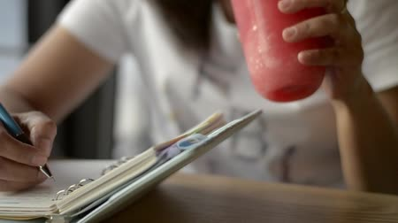 vodní meloun : Asian woman writing on diary to inspire life and drinking a cup of smoothie fruit juice on the table in coffee shop. Dostupné videozáznamy