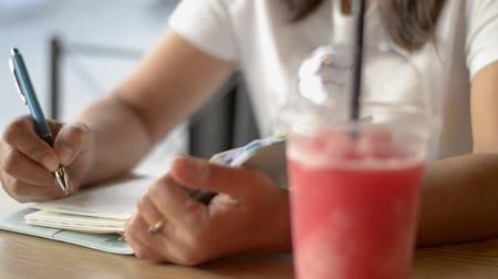 Asian woman writing on diary to inspire life and drinking a cup of smoothie fruit juice on the table in coffee shop. Stock Footage