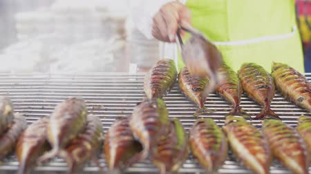 Fishes grilled on a charcoal grill preparing by a male chef in local food market in thailand. Close up and panning shot.