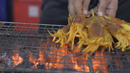 kalmar : Grilled squids on a charcoal grill with a mans hands rotating the skewers. Local street food in thailand.