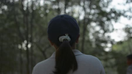 Young beautiful woman wearing cap walking through a pathway in a mangrove forest in phuket. Rear view follow shot. Stock Footage