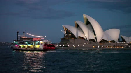 opera lirica : Showboat in movimento vicino alla Sydney Opera House al crepuscolo Filmati Stock