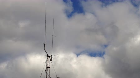 Long shot of a Home based dual Telecommunications antenna tower with spike storm clouds time lapse with no birds in it.