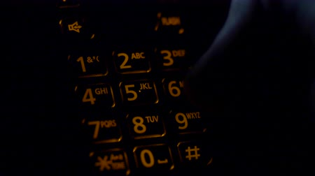 Extreme close up of a cordless phone keypad touchtone dialing 911 emergency call in nightime.