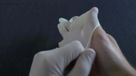 A medium shot of putting on surgical white gloves