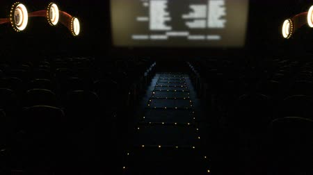 Medium long shot of empty movie theater with final credits rolling