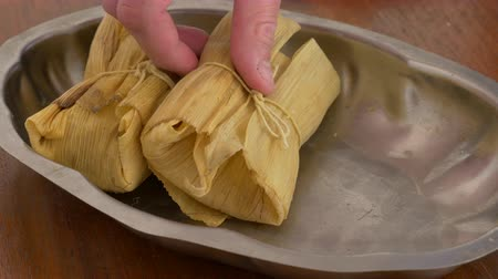 Sideshot shot of a tray been filled with tamales for serving