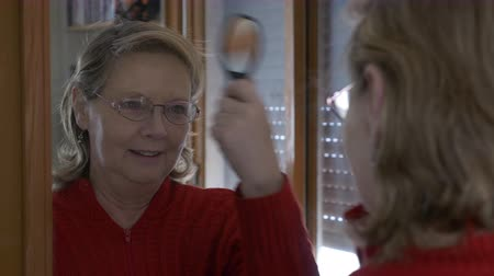 Medium shot of a middle aged woman combing herself in the mirror with happy expression Wideo