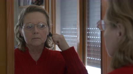 Medium shot of a middle aged woman combing herself in the mirror with serious expression