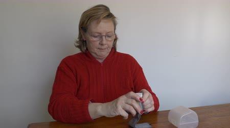 Medium shot of a Middle aged woman taking a reading reading with her wrist monitor