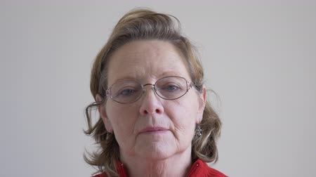 Close-up of a Middle aged woman with serious expression taking her glasses off