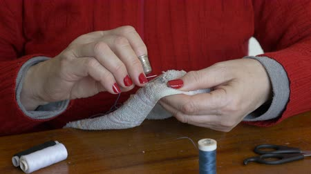 Close up of an Adult woman sewing a rag by hand Wideo
