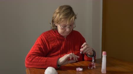 Medium shot of a Middle aged woman painting her fingernails