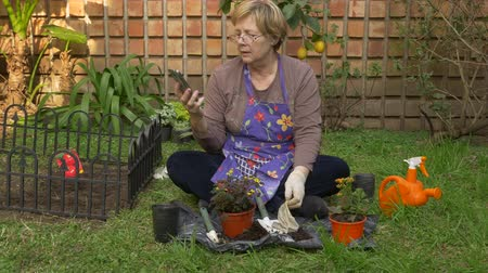 Full shot of an adult woman answering a video call while working in her garden