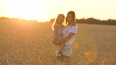 beautiful young mother and her daughter having fun at the wheat field