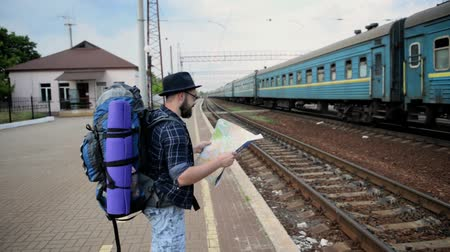 Traveler man with map and waits train on railway platform