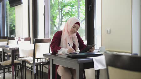 vállkendő : Beautiful muslim woman in cafe with tablet Stock mozgókép