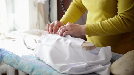 Tailor ironing the fabric. seamstress irons dress in a sewing workshop Стоковые видеозаписи