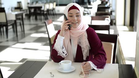 Muslim Woman Talking on Mobile Phone in a Cafe Стоковые видеозаписи