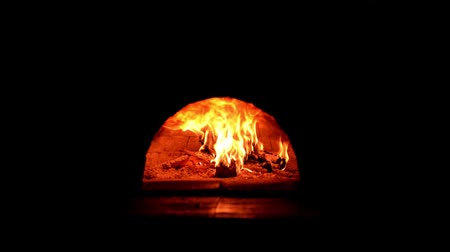 Fire burning in a forno Pompeii brick pizza oven.
