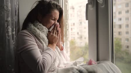 A cold, chilled woman sneezes. Girl blowing his nose while sitting at the window. Стоковые видеозаписи