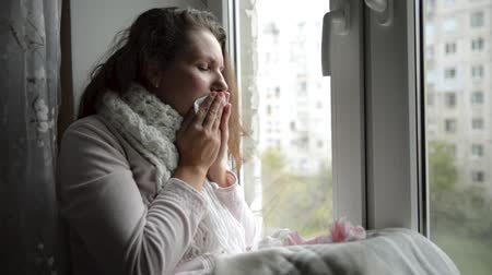 A cold, chilled woman sneezes. Girl blowing his nose while sitting at the window. Vídeos