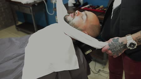 man shaving his beard in the professional hairdresser Стоковые видеозаписи