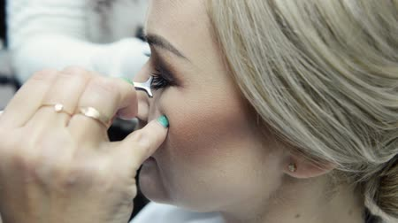 Makeup artist applying false eyelashes to models eyes. Vídeos