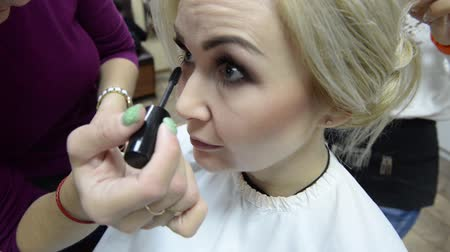 Make-up artist makes make-up eyelashes in a young woman.Makeup. Cosmetic. Base for Perfect Make-up.Applying Make-up. Стоковые видеозаписи