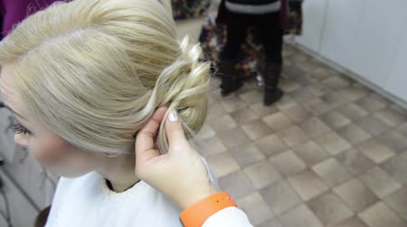 Hairdresser makes evening hairstyle close-up on blond hair of business woman in beauty salon Стоковые видеозаписи