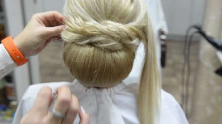 business style : Hairdresser makes evening hairstyle close-up on blond hair of business woman in beauty salon Stock Footage