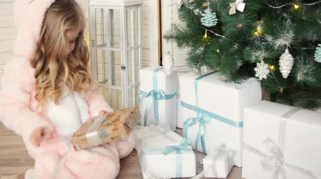Happy Christmas little girl opening a wrapped Xmas gift box near decorated Christmas tree. Laughing child celebrating Christmas and New Year Winter Holidays. Vídeos