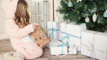 Happy Christmas little girl opening a wrapped Xmas gift box near decorated Christmas tree. Laughing child celebrating Christmas and New Year Winter Holidays. Стоковые видеозаписи