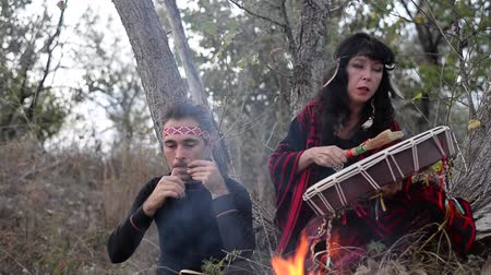 eu : shamanic woman playing on shaman frame drum in the nature around the fire and a man playing a harp
