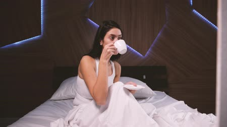 waking : Attractive young girl at home. Drinking coffee in her bed Stock Footage