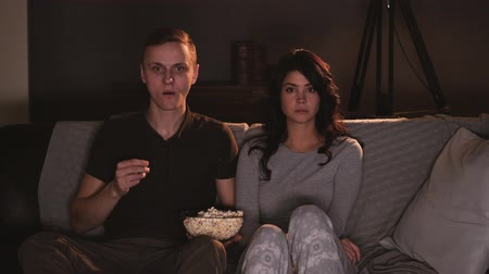 попкорн : Young couple watching something on tv at home and eating popcorn