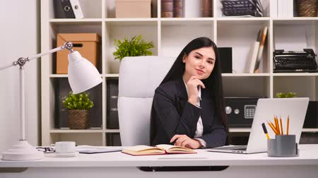 офисные кресла : Pretty businesswoman in her office. Looking at the camera and smiling. 4k