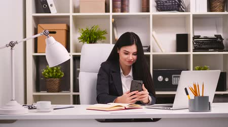 mensageiro : Pretty businesswoman in her office. Texting to someone with her smartphone. 4k