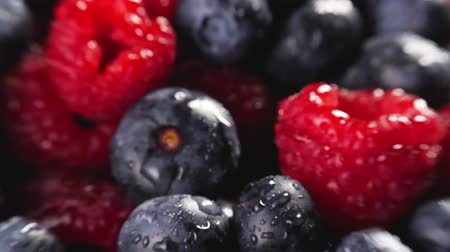 picked : Heap of fresh blueberries and raspberries rotating. Shallow depth of field. Follow focus. Closeup macro shot. Fresh berry series. 4k.