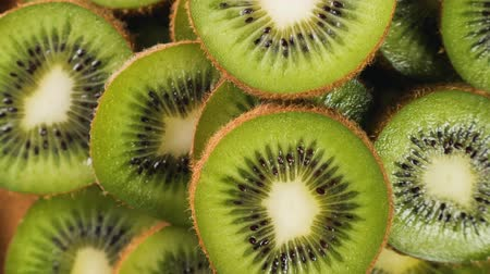 キウイ : Heap of fresh sliced kiwi fruits rotating. Closeup macro shot. Fresh berry series. 4k.