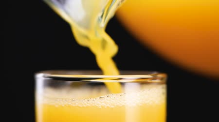 ananas : Orange juice pouring in the glass from the jug. Orange or pineapple juice. Making bubbles. Slow motion.