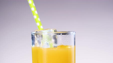 ice cube : Someone drinking orange or pineapple juice from the glass throw the straw.
