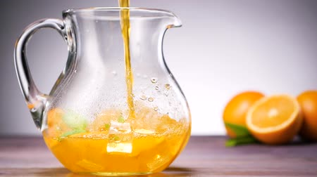 karbonatlı : Orange juice pouring in the glass. Making bubbles. Slow motion. Shallow depth of field. Stok Video