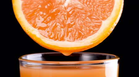 picked : sliced orange fruit with drops of juice falling from it in glass in slow motion. Closeup macro shot. Fresh berry and fruit series. Stock Footage