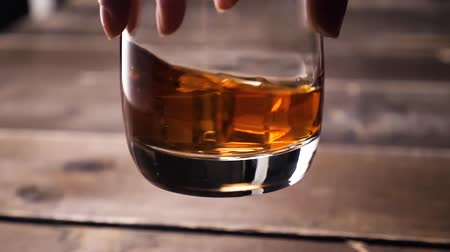 cognac : Golden whiskey rotating in the glass. With ice cubes. Stock Footage