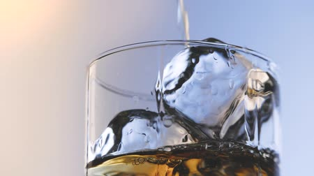 mout : Glas whisky met ijsblokje. Alcohol gieten in het glas. Scotch op de rotsen. Stockvideo