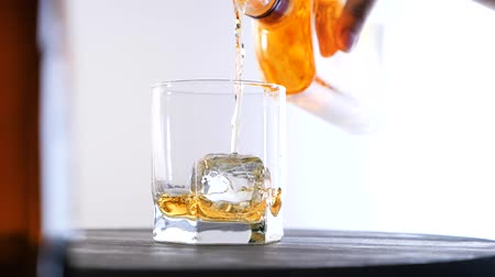 mout : Glass of whiskey with ice cube. Alcohol pouring in the glass from the bottle. Scotch on the rocks. Slider shot.