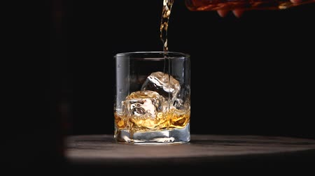 pálinka : Glass of whiskey with ice cube. Alcohol pouring in the glass from the bottle. Scotch on the rocks. Slider shot. Dark, rustic, background.