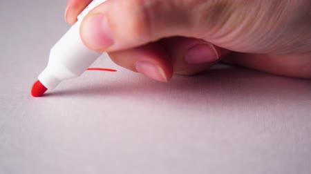macro : Drawing a red heart on white paper with a marker. Closeup.