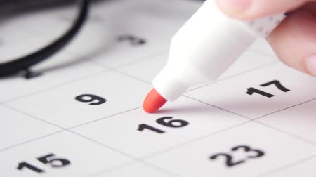 organizatör : Signing a day on a calendar with red pen or marker. Putting date in circle. Stok Video